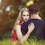 男性を抱きしめる金髪の女性