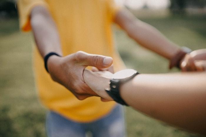 女性の手を引く黄色いシャツの男性