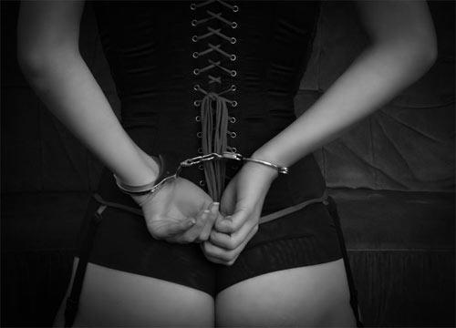 後ろ手に手錠をする女